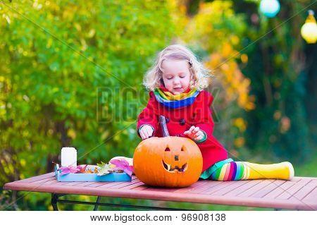 Little Girl Carving A Pumpkin At Halloween