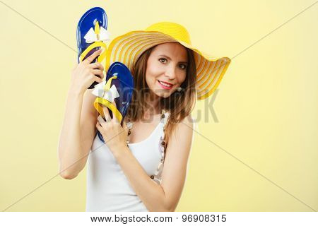 Woman In Big Yellow Summer Hat Holds Flip Flops