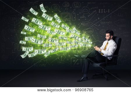 Businessman sitting in chair holding tablet with dollar bills coming out concept on background