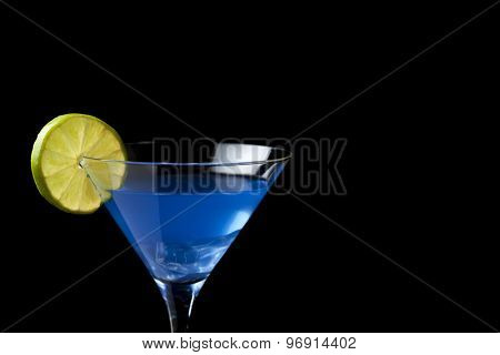 blue cocktail in martini glass with lime slice on black background with copy space