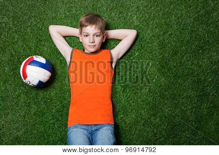 Boy lying with ball on green grass