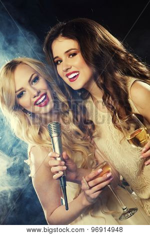 Karaoke party. Beauty girls with a microphone singing and dancing over dark background.