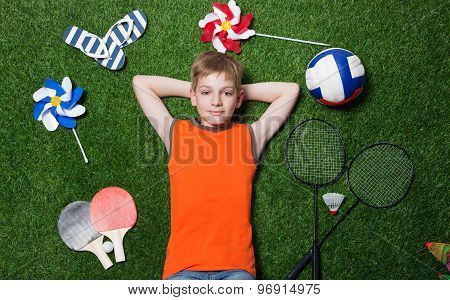 Boy lying with sport equipment on green grass