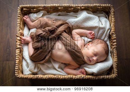 Newborn baby boy lying down inside the wicker basket