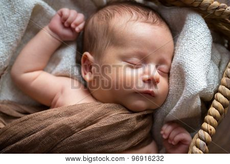 Newborn baby boy sleeping inside the wicker basket