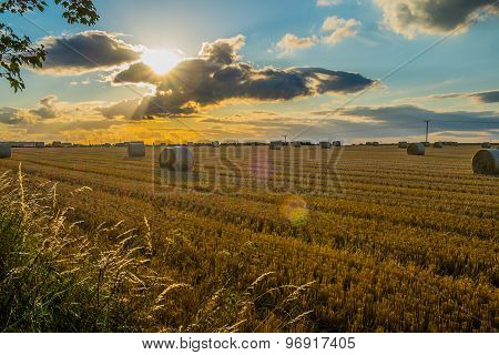 straw bales in a field at sunset with lens flare from sun