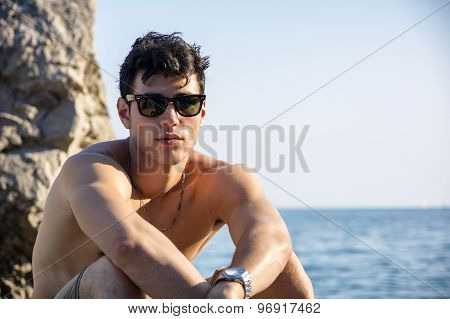 Handsome young man on beach with wet hair and sunglasses