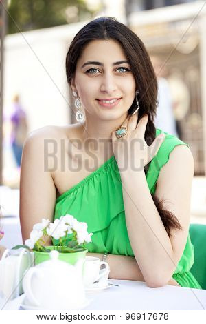 Happy Beautiful young arabic woman sitting in a coffee shop and drink tea