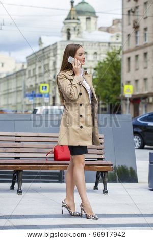 Business young woman in a beige raincoat talking on his cell phone on the street