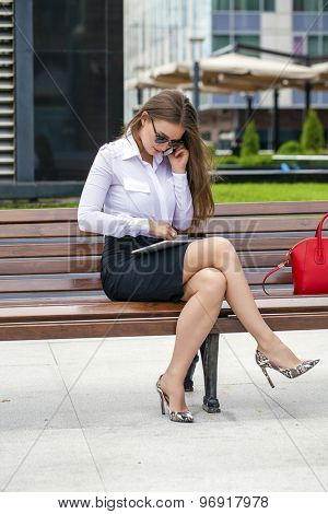 Young beautiful business woman sitting on a bench in the summer city