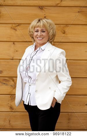 Happy elderly woman in a white jacket on the background of wooden wall
