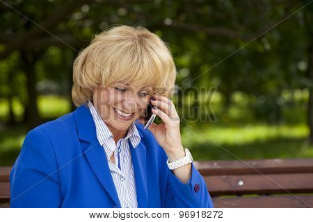 Close up portrait of an elderly beautiful blonde woman talking on a cell phone in a summer park