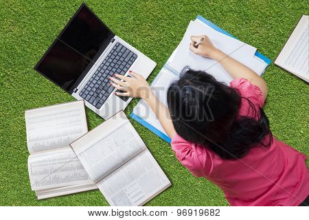 College Student Lying On Grass While Studying