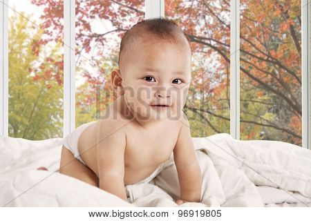 Cute Baby Smiling At Camera In Bedroom