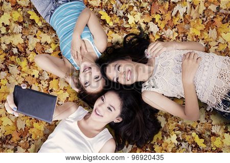 Girls Taking Photos On Autumn Leaves