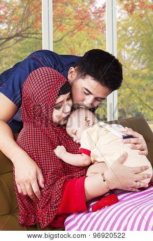Happy Muslim Parents Kiss Their Child