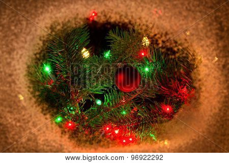 Red Ornament Hanging On Fir Tree Branch With Lights And Surrounding Snow Border