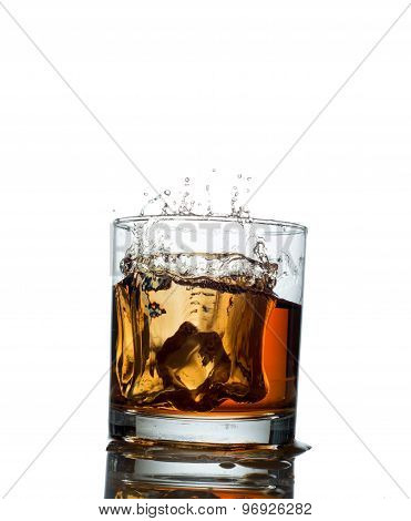 splash of whiskey with ice osolated on white