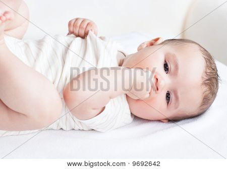 Portrait Of A Cute Newborn Baby Lying On The Sofa In His Bedroom