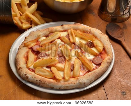 Fried potatoes pizza on rustic ambient.