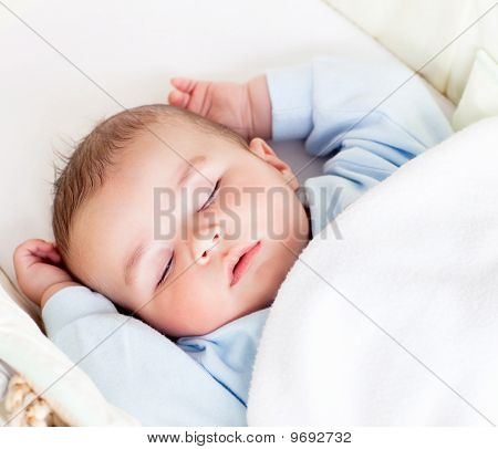Portrait Of A Peaceful Baby Sleeping In His Cradle At Home
