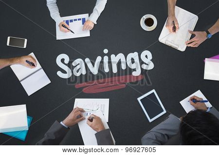 The word savings and business meeting against blackboard