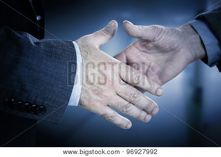Two people going to shake their hands against college hallway