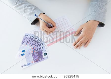 business, finance, gambling and people concept - close up of woman hands filling lottery ticket and money