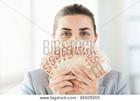 business, finance, saving, banking and people concept - close up of woman hiding her face behind euro money fan