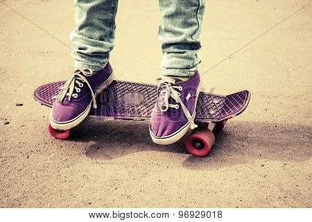 Teenager Feet In Jeans And Gumshoes On Skateboard