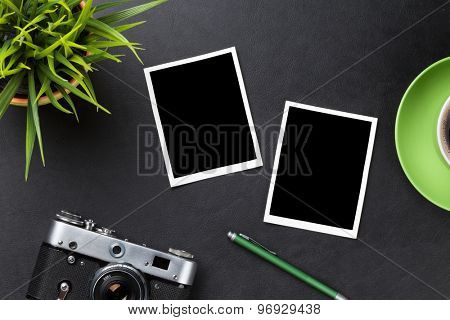 Photo frames over leather desk table, camera, coffee and flower. Top view