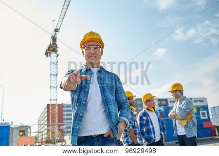 business, building, teamwork and people concept - group of smiling builders in hardhats pointing finger at you on construction site