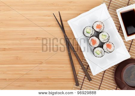 Sushi set, chopsticks and soy sauce over bamboo table with copy space