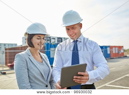 business, building, teamwork, technology and people concept - smiling man and woman in hardhats with tablet pc computer at construction site
