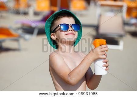 Boy Applying Sunscreen Spray On Beach