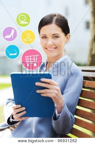 business, technology, online shopping and people concept - young smiling woman with tablet pc computer and internet icons sitting on bench in city