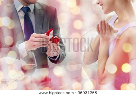 couple, love, engagement and holiday concept - close up of excited young woman and boyfriend giving her ring at restaurant over pink holidays lights background
