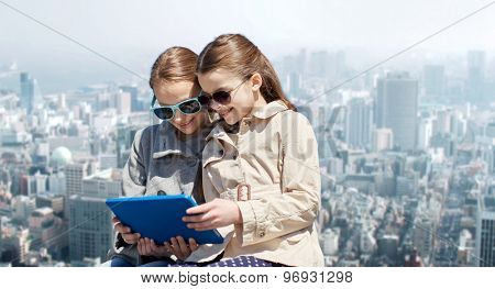 people, children, technology, friends and friendship concept - happy little girls in sunglasses with tablet pc computer over city background