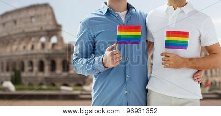 people, homosexuality, same-sex marriage, travel and love concept - close up of happy male gay couple holding rainbow flags and hugging from back over coliseum in rome background