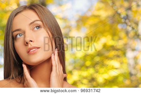 beauty, people and health concept - beautiful young woman touching her neck over yellow autumn background