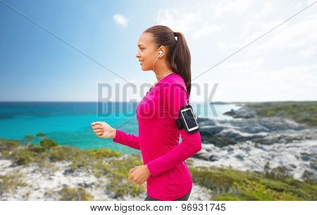 sport, fitness, technology and people concept - smiling young african american woman running with smartphone and earphones over beach background