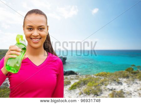 fitness, people and sport concept - smiling african american woman drinking from bottle over beach background