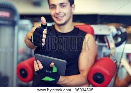 sport, bodybuilding, technology, gesture and people concept - happy young man with tablet pc computer showing thumbs up in gym