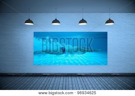 Fit swimmer training on his own against grey room