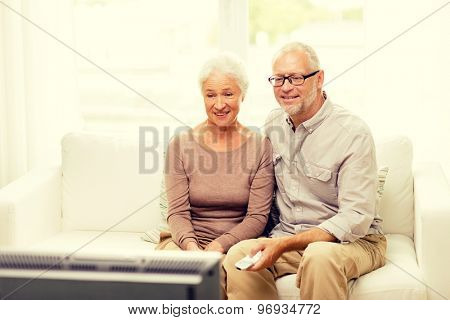 family, technology, age and people concept - happy senior couple watching tv at home