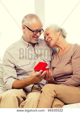 family, holidays, age and people concept - happy senior couple with little red gift box at home