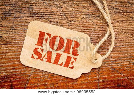 for sale sign a paper price tag against rustic red painted barn wood - shopping concept
