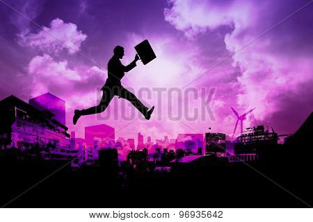 Businessman with briefcase against purple sky over city
