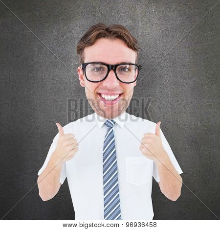 Geeky businessman with thumbs up against grey room