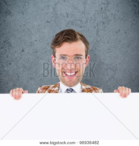 Geeky businessman showing card against dirty old wall background
